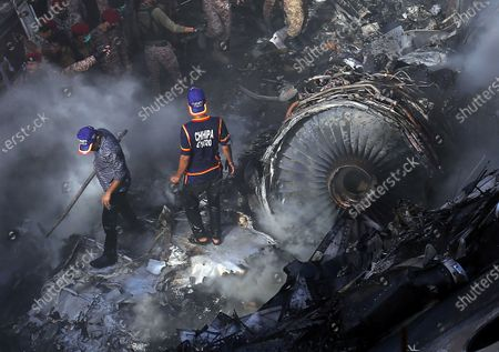 Rescue workers search for the bodies or survivors amid wreckage of the passenger plane of state run Pakistan International Airlines, after it crashed on a residential colony, in Karachi, Pakistan, 22 May 2020. A Pakistan International Airlines passenger flight with over 100 people on board crashed on 22 May as it was about to land near a residential area close to the airport in the port city of Karachi, a civil aviation official said. Rescue workers reportedly spot the Black Box.