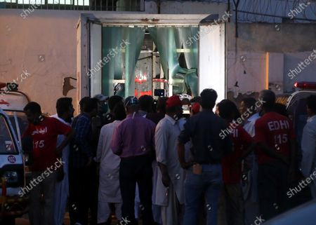 People gather outside a mobile mortuary unit of rescue service after bodies of the victims of the  plane crarh are recovered in Karachi, Pakistan, 22 May 2020. A Pakistan International Airlines passenger flight with over 100 people on board crashed on 22 May as it was about to land near a residential area close to the airport in the port city of Karachi, a civil aviation official said.