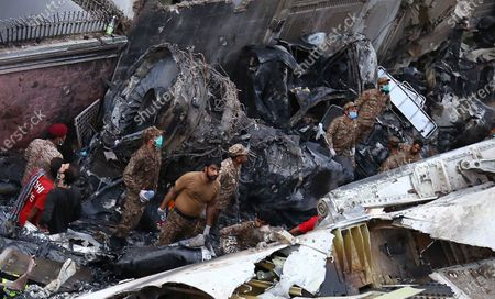 Rescue workers search for the bodies of survivors in the wreckage of the passenger plane of state run Pakistan International Airlines, after it crashed on a residential colony, in Karachi, Pakistan, 22 May 2020. A Pakistan International Airlines passenger flight with over 100 people on board crashed on 22 May as it was about to land near a residential area close to the airport in the port city of Karachi, a civil aviation official said.