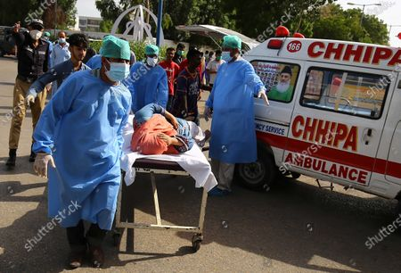 A woman who was injured when a passenger plane of state run Pakistan International Airlines, crashed on a residential colony, is shifted to a hospital, in Karachi, Pakistan, 22 May 2020. A PIA Airbus A-320 flight from Lahore to Karachi carrying some 107 passengers and crew, crashed while landing in Karachi on 22 May.