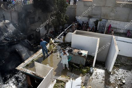 Locals inspect the destruction caused after a passenger plane of state run Pakistan International Airlines, crashed on a residential colony, in Karachi, Pakistan, 22 May 2020. A PIA Airbus A-320 flight from Lahore to Karachi carrying some 107 passengers and crew, crashed while landing in Karachi on 22 May.