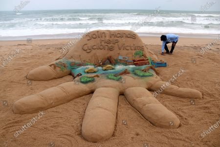 Indian sand artist Sudarsan Pattnaik gives final touches to a sand sculpture made on the theme of Cyclone Amphan with a message, 'Join hands, Help Cyclone victims,' at Puri beach, in Odisha, India, 22 May 2020. Amphan, the first tropical cyclone of the 2020 season in the North Indian basin, made landfall on 20 May 2020. The storm slammed ashore near the border of eastern India and Bangladesh, delivering substantial storm surge to coastal areas. The Indian states of Odisha and West Bengal were heavily affected by Amphlan, with 80 people reportedly killed in Bengal and the state capital Kolkata bearing heavy damages.