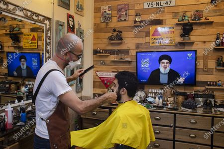 Barber wearing a mask to help stop the spread of the new coronavirus listens to a speech by Hezbollah leader Sayyed Hassan Nasrallah being broadcast on Hezbollah's al-Manar TV channel, to mark Al-Quds (Jerusalem) day while he cuts a customer's hair at his salon, in the southern suburb of Beirut, Lebanon