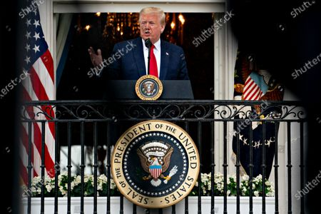 United States President Donald J. Trump speaks from the Blue Room Balcony of the White House during a Rolling to Remember ceremony honoring the nation's veterans and prisoners of war/missing in action (POW/MIA) in Washington, D.C., U.S.,. Trump didn't wear a face mask during most of his tour of Ford Motor Co.'s ventilator facility Thursday, defying the automaker's policies and seeking to portray an image of normalcy even as American coronavirus deaths approach 100,000.