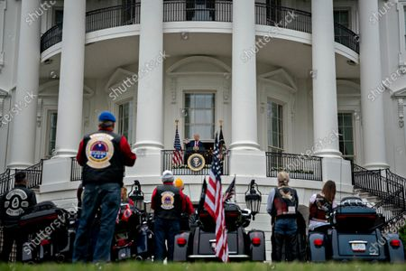 Stock Image of United States President Donald J. Trump, center, speaks from the Blue Room Balcony of the White House during a Rolling to Remember ceremony honoring the nation's veterans and prisoners of war/missing in action (POW/MIA) in Washington, D.C., U.S.,. Trump didn't wear a face mask during most of his tour of Ford Motor Co.'s ventilator facility Thursday, defying the automaker's policies and seeking to portray an image of normalcy even as American coronavirus deaths approach 100,000.
