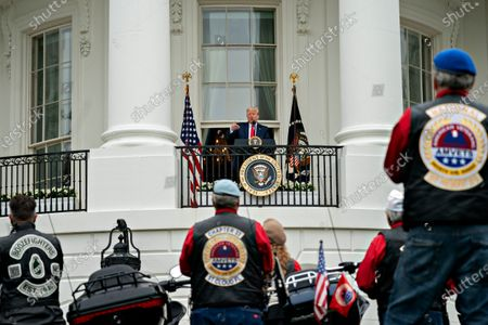 United States President Donald J. Trump, center, speaks from the Blue Room Balcony of the White House during a Rolling to Remember ceremony honoring the nation's veterans and prisoners of war/missing in action (POW/MIA) in Washington, D.C., U.S.,. Trump didn't wear a face mask during most of his tour of Ford Motor Co.'s ventilator facility Thursday, defying the automaker's policies and seeking to portray an image of normalcy even as American coronavirus deaths approach 100,000.