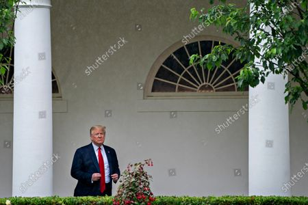 United States President Donald J. Trump adjusts his jacket while standing in the Colonnade of the White House after a Rolling to Remember ceremony honoring the nation's veterans and prisoners of war/missing in action (POW/MIA) in Washington, D.C., U.S.,. Trump didn't wear a face mask during most of his tour of Ford Motor Co.'s ventilator facility Thursday, defying the automaker's policies and seeking to portray an image of normalcy even as American coronavirus deaths approach 100,000.