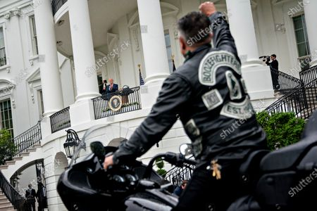 United States President Donald J. Trump, center left, watches as actor Robbert Patrick ride a motorcycle past the White House during a Rolling to Remember ceremony honoring the nation's veterans and prisoners of war/missing in action (POW/MIA) in Washington, D.C., U.S.,. Trump didn't wear a face mask during most of his tour of Ford Motor Co.'s ventilator facility Thursday, defying the automaker's policies and seeking to portray an image of normalcy even as American coronavirus deaths approach 100,000.