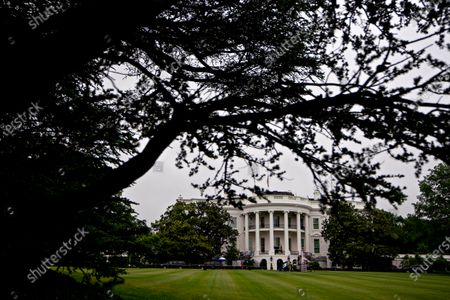 The White House stands past the South Lawn in Washington, D.C., U.S.,. United States President Donald J. Trump didn't wear a face mask during most of his tour of Ford Motor Co.'s ventilator facility Thursday, defying the automaker's policies and seeking to portray an image of normalcy even as American coronavirus deaths approach 100,000.