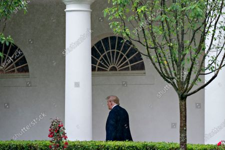 United States President Donald J. Trump walks through the Colonnade of the White House after a Rolling to Remember ceremony honoring the nation's veterans and prisoners of war/missing in action (POW/MIA) in Washington, D.C., U.S.,. Trump didn't wear a face mask during most of his tour of Ford Motor Co.'s ventilator facility Thursday, defying the automaker's policies and seeking to portray an image of normalcy even as American coronavirus deaths approach 100,000.