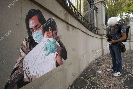 Stock Picture of A view of a coronavirus-inspired mural by the street artist Harry Greb, painted on the external wall of the Spallanzani hospital in Rome, Italy, 22 May 2020. The artwork is a tribute to those who could not embrace their sick loved ones and those who recovered or passed without having been embraced. Greb chose an image from Milos Forman's film 'One Flew Over the Cuckoo's Nest.' It shows the embrace between the two protagonists played by US actors Jack Nicholson and Will Sampson, depicted hugging each other while wearing masks and gloves. Italy is gradually easing lockdown measures implemented to stem the spread of the SARS-CoV-2 coronavirus that causes the COVID-19 disease.