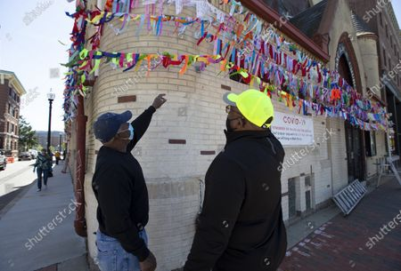 Macarthur Adams (L) working with Reverend Pedro Castro (R) discuss where to hang an additional line of some of over 6000 ribbons on the exterior of the Grant African Methodist Episcopalian Church as part of a memorial display, in Boston, Massachusetts, USA 22 May 2020. In an effort to show compassion and a memorial for the victims of the coronavirus, church members have been hanging ribbons to represent each of the dead each week.