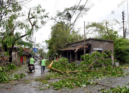 People walk through broken trees and poles during the aftermath. Cyclone Amphan has hit west Bengal with a speed of 150 Km/ hr. which caused huge destruction of lively hood and 76 deaths have been reported so far.