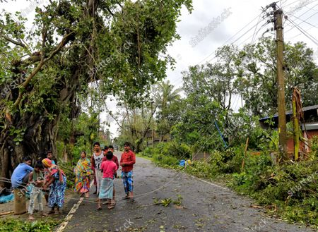People standing next to broken dangerous electricity wires laying on the ground during the aftermath. Cyclone Amphan has hit west Bengal with a speed of 150 Km/ hr. which caused huge destruction of lively hood and 76 deaths have been reported so far.