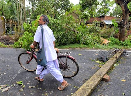 A man walks over an electric pole laying on the ground during the aftermath. Cyclone Amphan has hit west Bengal with a speed of 150 Km/ hr. which caused huge destruction of lively hood and 76 deaths have been reported so far.