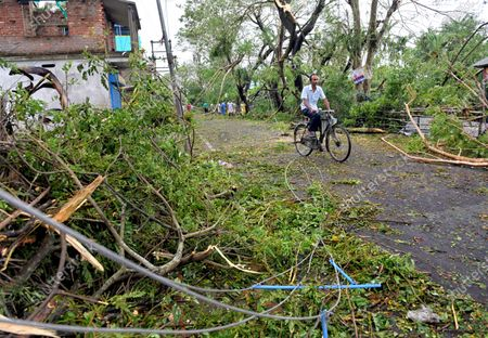 A man rides his bicycle through broken trees and poles during the aftermath. Cyclone Amphan has hit west Bengal with a speed of 150 Km/ hr. which caused huge destruction of lively hood and 76 deaths have been reported so far.
