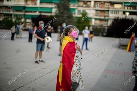 Stock Image of Woman with a Spanish flag on her shoulders takes part during a protest against the Spanish government amid the lockdown to prevent the spread of coronavirus in Alcorcon, Spain, . The Spanish government is allowing Madrid and Barcelona to ease their lockdown measures, which were introduced to fight the coronavirus pandemic