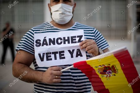 """Man holds a Spanish flag and banner reading in Spanish: """"Sanchez go away"""" during a protest against the Spanish government amid the lockdown to prevent the spread of coronavirus in Alcorcon, Spain, . The Spanish government is allowing Madrid and Barcelona to ease their lockdown measures, which were introduced to fight the coronavirus pandemic"""