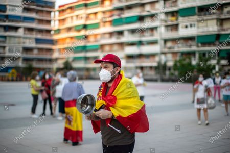 Man with a Spanish flag on his shoulders and banging a saucepan takes part in a protest against the Spanish government amid the lockdown to prevent the spread of coronavirus in Alcorcon, Spain, . The Spanish government is allowing Madrid and Barcelona to ease their lockdown measures, which were introduced to fight the coronavirus pandemic