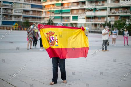 Woman holds a Spanish flag during a protest against the Spanish government amid the lockdown to prevent the spread of coronavirus in Alcorcon, Spain, . The Spanish government is allowing Madrid and Barcelona to ease their lockdown measures, which were introduced to fight the coronavirus pandemic