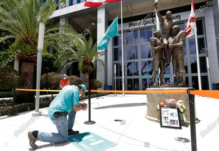 "Wearing a mask to guard against the coronavirus, former Miami Dolphins player Jim ""Crash"" Jensen kneels in front of a statue of coach Don Shula during a tribute procession, at Hard Rock Stadium in Miami Gardens, Fla. Shula died on May 4"