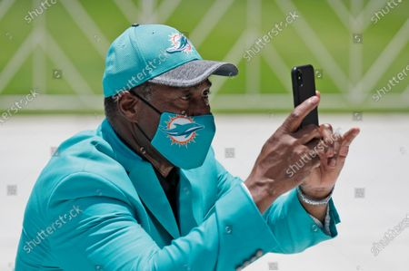 Wearing a mask to guard against the coronavirus, former Miami Dolphins player and current Senior Vice President, Special Projects, Alumni Relations & Advisor To CEO, Nat Moore, takes a photo of guests at a tribute procession for coach Don Shula, at Hard Rock Stadium in Miami Gardens, Fla. Shula died on May 4