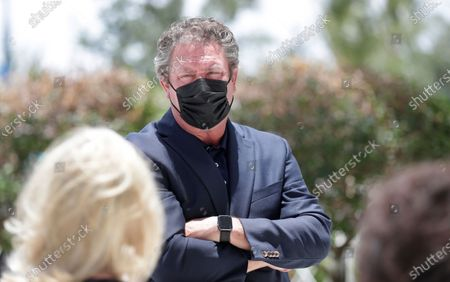 Wearing a mask to guard against the coronavirus, former Miami Dolphins quarterback and current Special Advisor To The Vice Chairman, President And CEO, Dan Marino, talks with guests at a tribute procession for late coach Don Shula, at Hard Rock Stadium in Miami Gardens, Fla. Shula died onn May 4