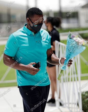 Wearing a mask to guard against the coronavirus, former Miami Dolphins player Terry Kirby, who was drafted by coach Don Shula in 1993, brings flowers to put at the base of a statue of Shula at a tribute procession for the coach, at Hard Rock Stadium in Miami Gardens, Fla. Shula died on May 4