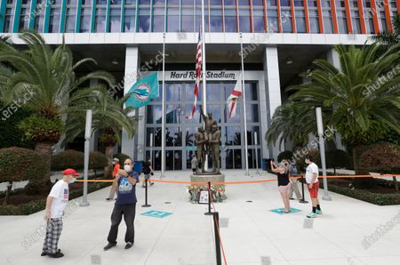 Wearing masks to guard against the coronavirus, football fans take photos at a tribute procession for coach Don Shula, at Hard Rock Stadium in Miami Gardens, Fla. Shula died on May 4