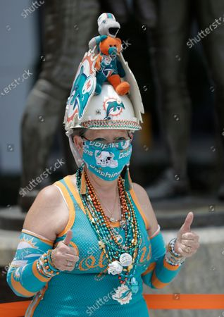 Stock Image of Wearing a mask to guard against the new coronavirus, Miami Dolphins fan Sue Cat poses for a photo in front of a statue of former coach Don Shula during a tribute procession for Shula, at Hard Rock Stadium in Miami Gardens, Fla. Shula died on May 4