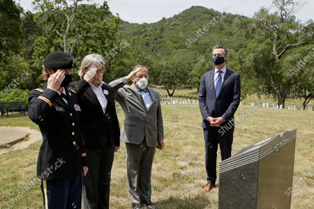 California Governor Gavin Newsom (R), watches as, (L-R) administrator, Lisa Peake, deputy administrator Stephanie Weaver and CalVet Secretary Vito Imbasciani salute after laying a wreath in the cemetery at the Veterans Home of California in Yountville, California, USA, 22 May 2020.