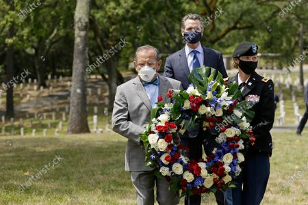 Stock Image of California Governor Gavin Newsom (R) watches as CalVet Secretary Vito Imbasciani (L),  and administrator Lisa Peake (R) lay a wreath in a cemetery at the Veterans Home of California in Yountville, California, USA, 22 May 2020.