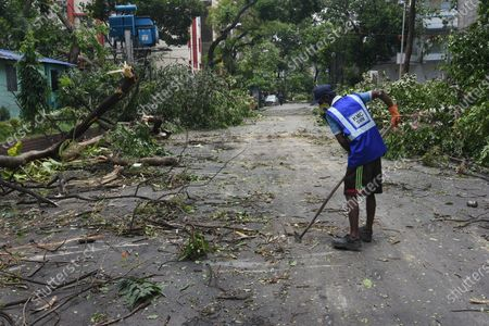 A Kolkata Municipal Corporation (KMC) worker cleaning road devastated by Cyclone Amphan.