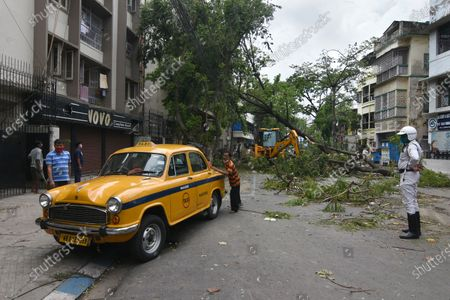 The Kolkata Police and The Kolkata Municipal Corporation struggling to bring back normal road devastated by cyclone Amphan. The Local people trying to shift position of a taxi for safety.