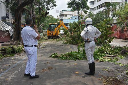 The Kolkata Police and The Kolkata Municipal Corporation struggling to bring back normal road devastated by cyclone Amphan.