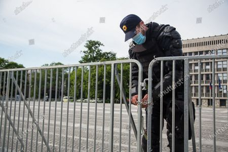 A policeman locks the fence around the parliament building before the anti-government protest. Thousands of people on bicycles and on foot again protested against the government, they accused Prime Minister Janez Jansa of using the covid-19 crisis situation for corruption and undemocratic rule.