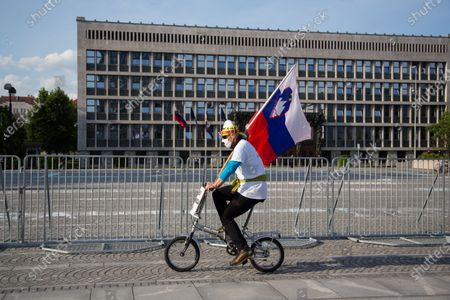 A protester wearing a face mask as preventive measure holds a Slovenian flag while riding during an anti-government protest. Thousands of people on bicycles and on foot again protested against the government, they accused Prime Minister Janez Jansa of using the covid-19 crisis situation for corruption and undemocratic rule.