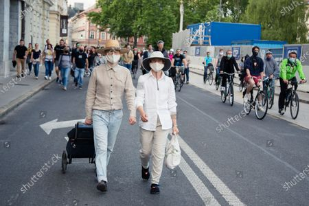 A couple wearing face masks as preventive measure walk down the street during an anti-government protest. Thousands of people on bicycles and on foot again protested against the government, they accused Prime Minister Janez Jansa of using the covid-19 crisis situation for corruption and undemocratic rule.