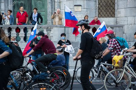 A woman wearing a face mask as preventive measure holds a Slovenian flag during an anti-government protest. Thousands of people on bicycles and on foot again protested against the government, they accused Prime Minister Janez Jansa of using the covid-19 crisis situation for corruption and undemocratic rule.