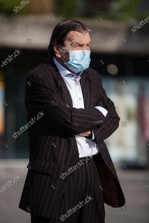An elegantly dressed man wearing a face mask as preventive measure takes part during an anti-government protest. Thousands of people on bicycles and on foot again protested against the government, they accused Prime Minister Janez Jansa of using the covid-19 crisis situation for corruption and undemocratic rule.