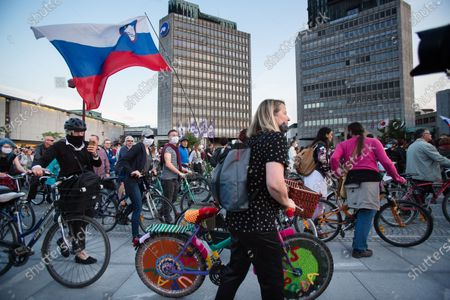 A woman pushes a bicycle with a knitted cover during the demonstration. Thousands of people on bicycles and on foot again protested against the government, they accused Prime Minister Janez Jansa of using the covid-19 crisis situation for corruption and undemocratic rule.