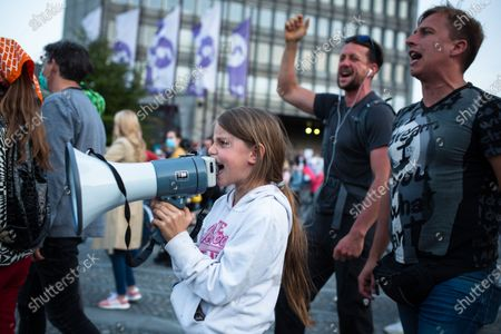 Stock Picture of A young girl shouts slogans on a megaphone during an anti-government protest. Thousands of people on bicycles and on foot again protested against the government, they accused Prime Minister Janez Jansa of using the covid-19 crisis situation for corruption and undemocratic rule.