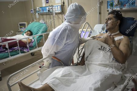 Dr. Rosa Lopez comforts her colleague Victor Cuba, an emergency room nurse infected with COVID-19, inside the Guillermo Almenara hospital in Lima, Peru, . Despite strict measures to control the virus, this South American nation of 32 million has become one of the countries worst hit by the disease