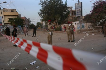 Pakistan army soldiers and police commandos stand guard while they cordon-off a street leading to the site of a plane crash, in Karachi, Pakistan, . A passenger plane carrying nearly 100 passengers crashed in a crowded neighborhood near the airport in Karachi
