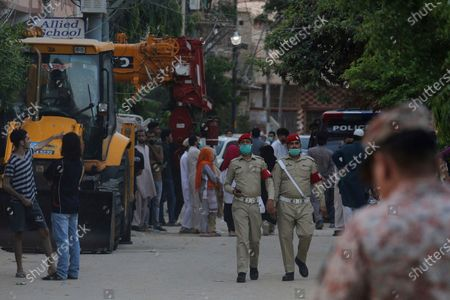 Local residents gather at a street blocked by security officials near the site of a plane crash, in Karachi, Pakistan, . A passenger plane carrying nearly 100 passengers crashed in a crowded neighborhood near the airport in Karachi