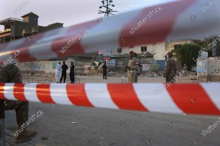 Pakistan army soldiers and police commandos stand guard while they cordon off a street leading to the site of a plane crash, in Karachi, Pakistan, . A passenger plane carrying nearly 100 passengers crashed in a crowded neighborhood near the airport in Karachi