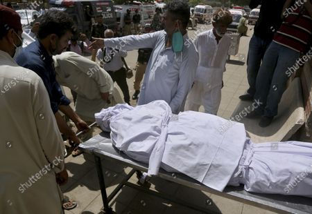 People load the body of a victim who was killed in the Friday's plane crash, into an ambulance at a morgue in Karachi, Pakistan, . An aviation official says a passenger plane belonging to state-run Pakistan International Airlines carrying passengers and crew crashed near the southern port city of Karachi Friday