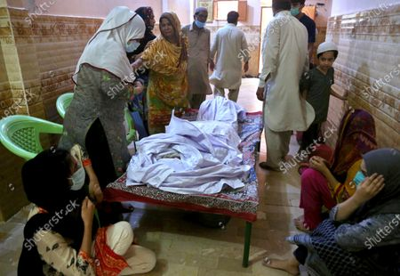 People mourn around the body of their relative, who was killed in the Friday's plane crash, at a morgue in Karachi, Pakistan, . An aviation official says a passenger plane belonging to state-run Pakistan International Airlines carrying passengers and crew has crashed near the southern port city of Karachi