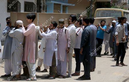 People carry the casket of the victims of Friday's plane crash for funeral prayers in Karachi, Pakistan, . An aviation official says a passenger plane belonging to state-run Pakistan International Airlines carrying passengers and crew has crashed near the southern port city of Karachi
