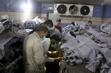 People identify body of their relative, who was killed in the Friday's plane crash, at a morgue in Karachi, Pakistan, . An aviation official says a passenger plane belonging to state-run Pakistan International Airlines carrying passengers and crew has crashed near the southern port city of Karachi